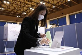 A masked woman votes in South Korea