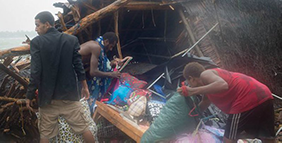 People cleaning up after Cyclone Pam