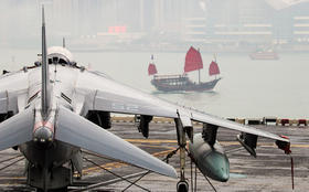 Chinese military jet taxis near a traditional junk boat