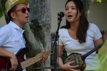 A man and a woman play musical instruments and sing